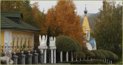 Trees with autumn colored foliage and small bright houses along the roadway